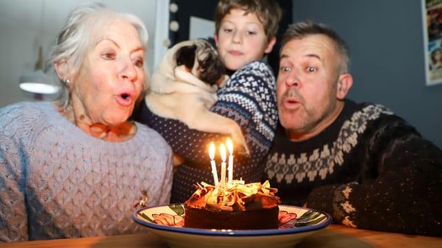 Eine ältere Frau sitzt mit einem Mann und einem Kind an einem Tisch und bläst drei Kerzen auf einer Torte aus.