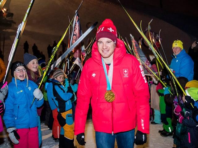 Fans stehen mit Skis Spalier