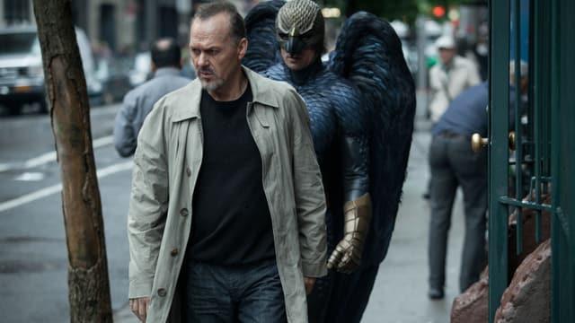 Michael Keaton in Jeans, schwarzem T-Shirt und Trenchcoat.