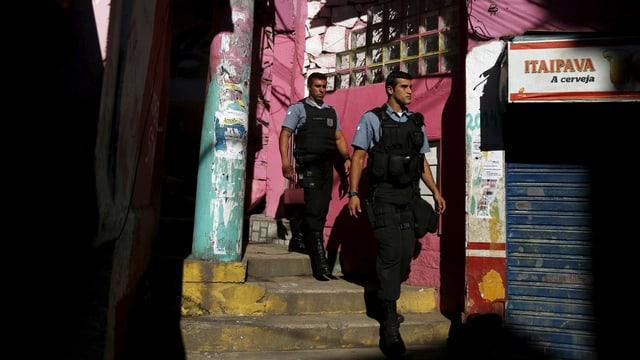 Polizisten mit schusssicheren Westen in einer Gasse.