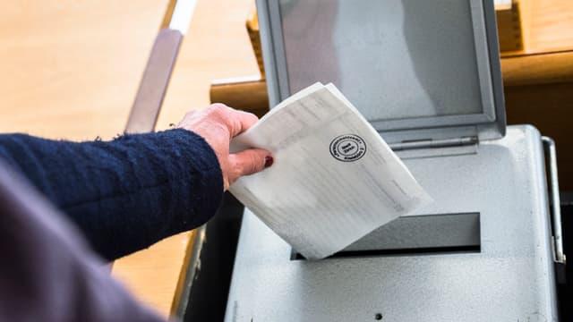 Ina dunna metta il cedel da votar en l'urna.