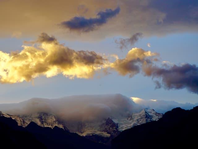 Bergkette mit etwas Schnee. Wolken hängen von hinten über die Berge und lösen sich vorne auf. Dämmerung.
