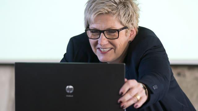 Eine Frau vor einem Laptop.
