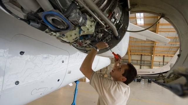 Arbeiter schraubt in Hangar an Flugzeugturbine.