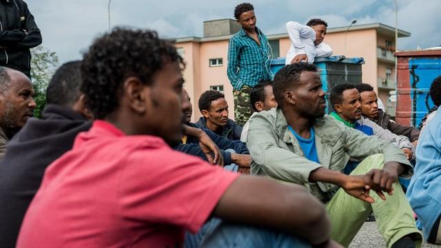 Männer aus Eritrea sitzen auf dem Boden vor einer Zivilschutzanlage.