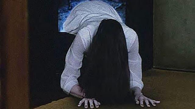 Ein Mädchen mit langen schwarzen Haaren vor dem Gesicht steigt aus einem Bildschirm.