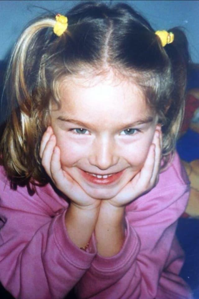 Kleines Mädchen mit zwei Zöpfen. Stützt Kopf auf Händen ab.