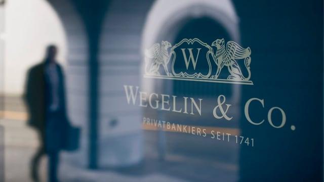 Das Logo der Bank Wegelin. Im Hintergrund ein Mann.