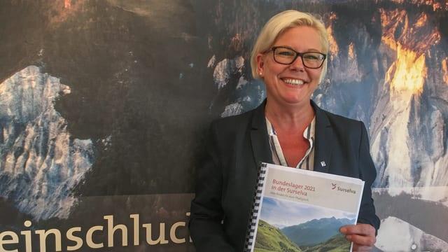 Anja Beivi, manadra da Surselva Turissem cun dossier da candidatura.