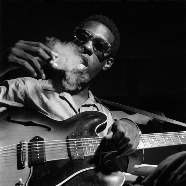 Grant Green raucht und hält eine Gitarre.