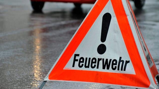"""Dreibeiniges, dreieckiges """"Achtung Feuerwehr""""-Signal steht auf nasser Strasse."""