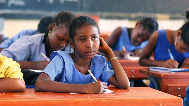 Kinder sitzen in einer Klasse. Ein Mädchen schaut nach vorne.