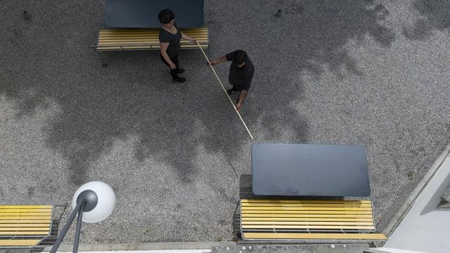 Zwei Personen messsen Tischabstand auf Restaurantterasse