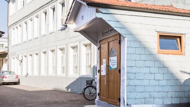 Ein kleines Häuschen mit einer Tür, welche in ein Gebäude führt.