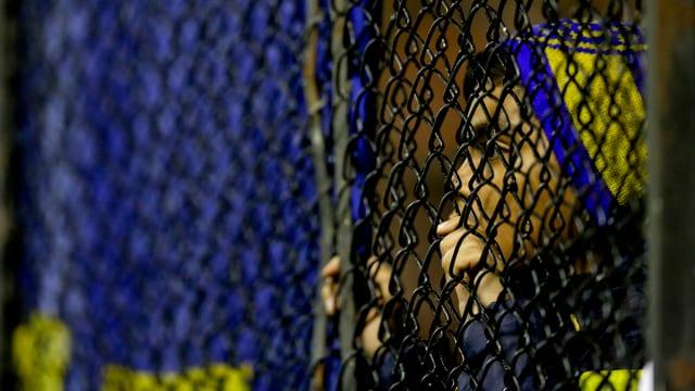 Ein Anhänger der Boca Juniors blickt durch einen Zaun