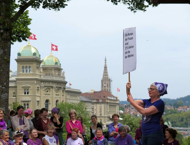 Frau vor Publikum mit Plakat