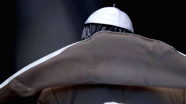 Papst mit wehendem weissem Umhang von hinten fotografiert.