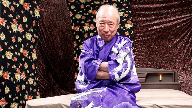 Ein Mann sitzt in einem Kimono auf einem Bett.