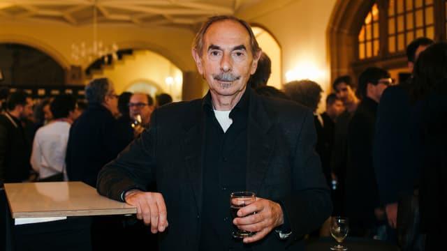 Ein mann an einem Stehtisch mit einem Glas in seiner Linken.