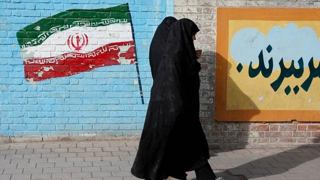 Zwei Frauen gehen an einer Wand mit einer aufgemalten iranischen Flagge vorbei.