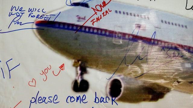 Auf einem Flugzeugplakat haben Angehörige Botschaften verewigt.