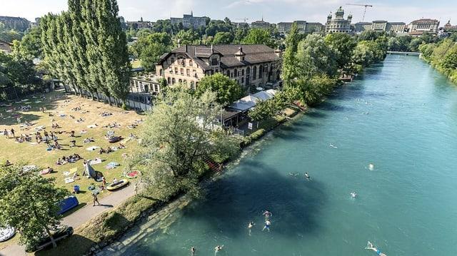 Bern: im Hintergrund das Bundeshaus, im Vordergrund die Aare mit schwimmenden Leuten.