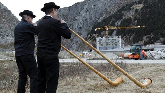 Zwei Männer blasen Alphorn, im Hintergrund ist eine Baustelle.