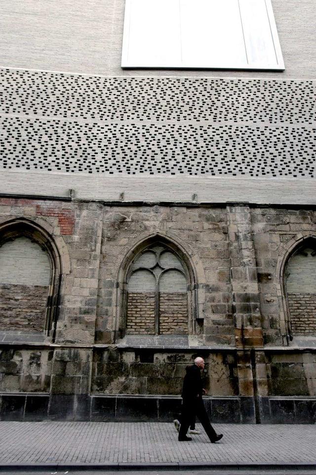 Ein Mann läuft vor einem Gebäude, das alte und neue Bauwerke verbindet.