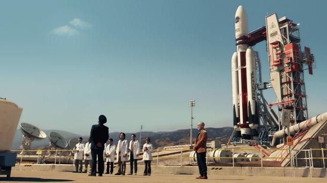 Von Weitem ein Platz, darauf steht eine Rakete und davor eine Gruppe winzig scheinender Menschen. Einer trägt eine Uniform, einer einen Anzug, die restlichen tragen weisse Kittel.
