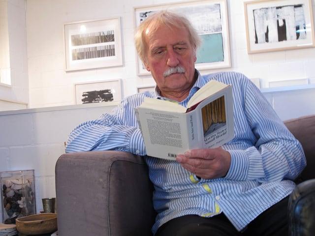 Ernst Wohlwend sitzt lesend in einem Sessel.