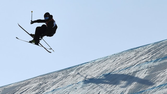 Andri Ragettli en l'aria vid siglir cun skis da freeski.