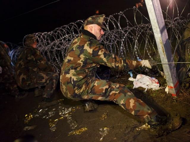 Soldat arbeitet am Grenzzaun.