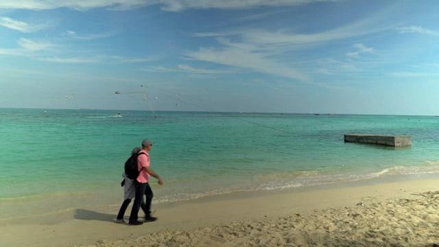 zwei Menschen gehen am Strand.