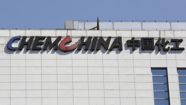 Das Firmenlogo von ChemChina an einem Gebäude.