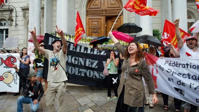 Demonstranten mit Bannern und roten Fahnen.