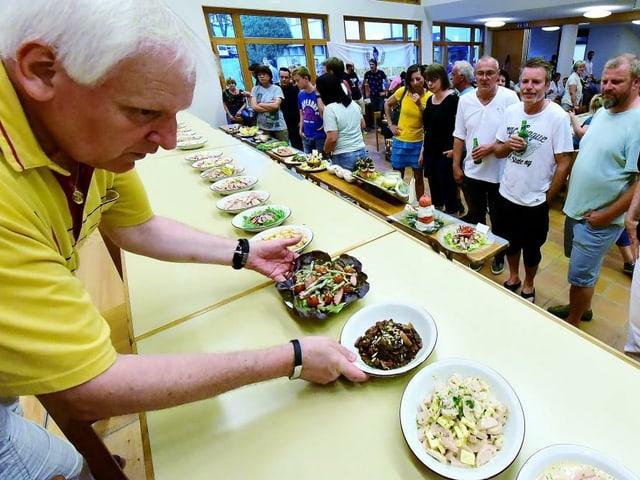 Mann stellt Teller auf langen Tisch. Menschen stehen davor.