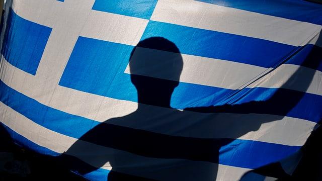 Schatten eines Mannes hinter einer Griechenlandfahne.