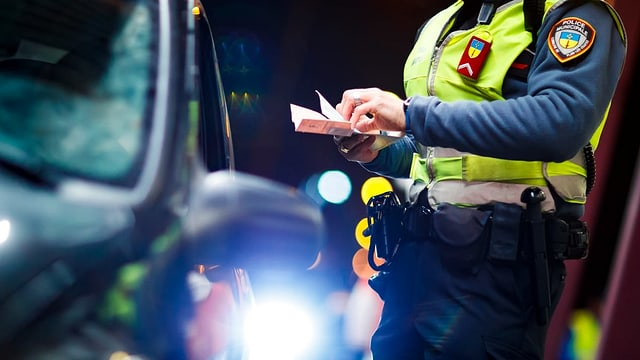 In policist dat giu in chasti ad in automobilist en il stgir.