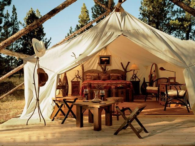 Grosses Zelt mit einem Doppelbett, Tischen und Stühlen.