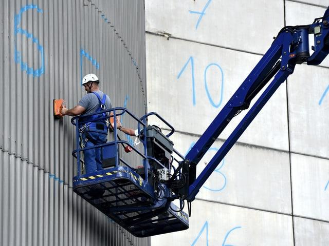 Mitarbeiter stehen auf einer Platform und messen and der AKW-Aussenhülle die Radioaktivität.