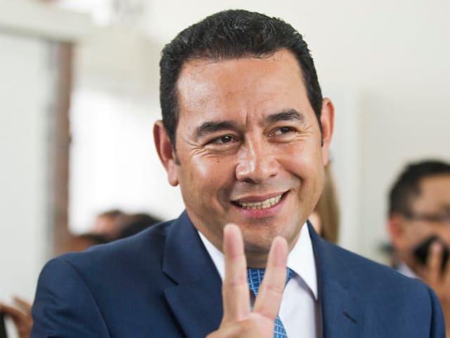 Jimmy Morales macht das V-Zeichen und lächelt dabei.