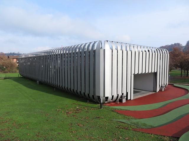 Ein futuristisches Gebäude ohne Fenster. Von aussen sieht man nur Metalllamellen.