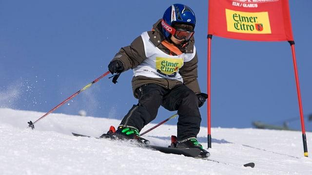 In mattin cun tschaplina blaua, giacca brina e chautschas nairas durant ina cursa da skis passa speravia ad ina porta cotschna.