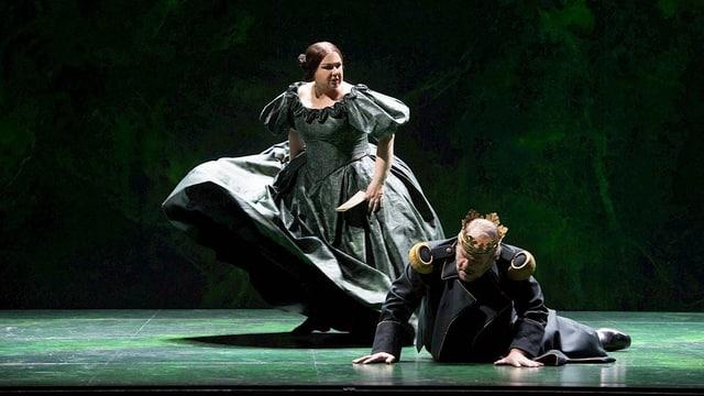 Frau mit Kleid steht. Davor liegt ein Mann mit Krone am Boden.