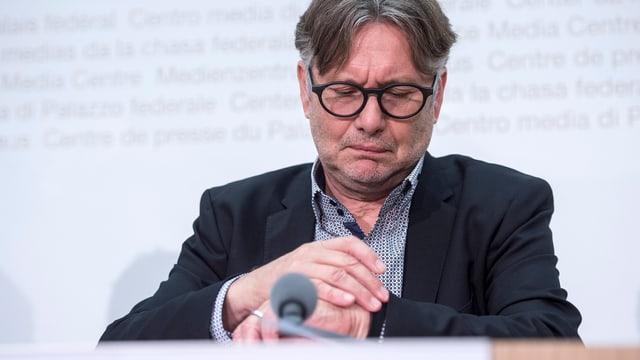 Hanspeter Thür an einer Medienkonferenz blickt auf seine Armbanduhr
