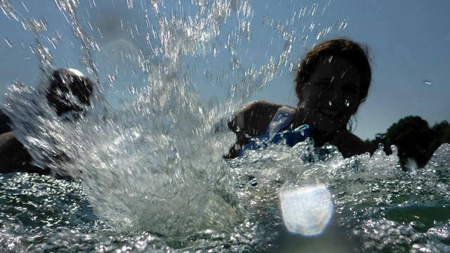 Frau schwimmt im Rhein. Man sieht sie kaum, dafür sieht man spritzendes Wasser.