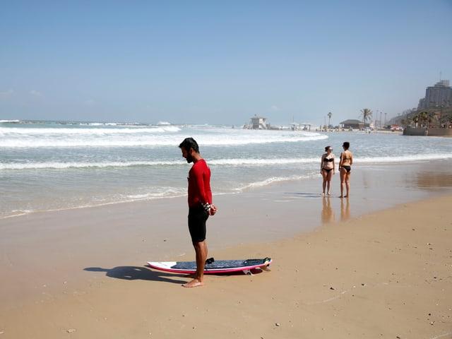 Ein Surfer hält am Strand inne.