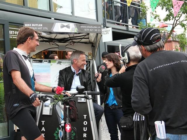 Mona Vetsch eröffnet die Sendung und begrüsst Dani Fohrler, der das Quartier in einer Rikscha erkunden wird.