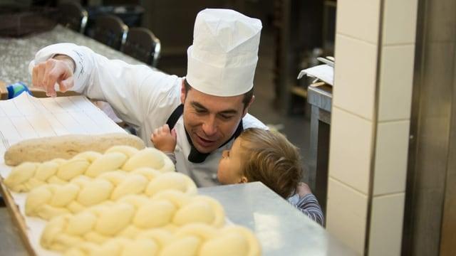 Ein Mann mit Kochhut ist dabei, Zöpfe zu backen und sein kleiner Sohn schaut zu.