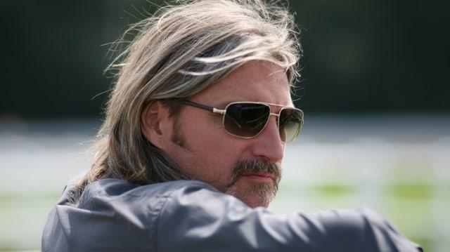 Ein Mann mit langen Haaren, Schnurrbart und Sonnenbrille.